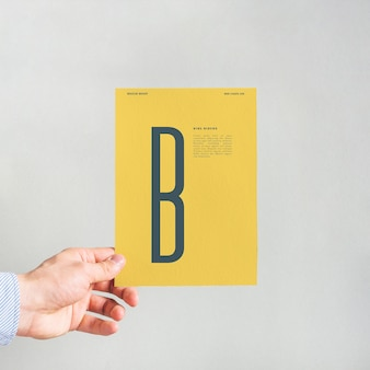 Mano sujetando mockup de página amarilla