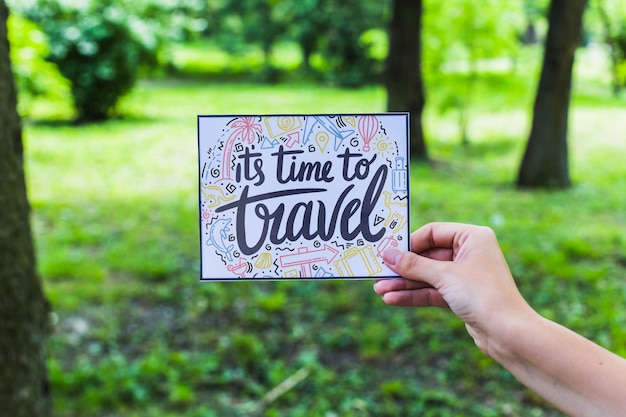 Mano sujetando papel en naturaleza para concepto de viajar