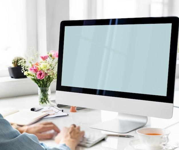 Manos escribiendo con una pantalla de computadora maqueta