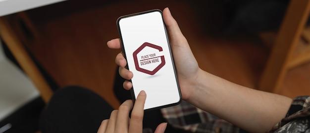 Manos de estudiante con smartphone de maqueta en office