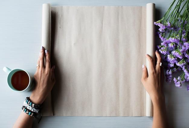 Manos de la gente que muestran el rollo de papel en blanco espacio de diseño vacío