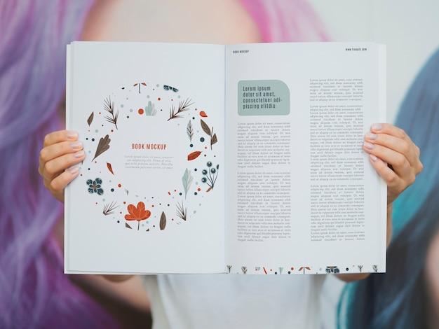 Manos mostrando páginas de una revista simulada