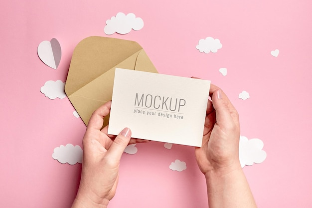 Manos sosteniendo maqueta de tarjeta de felicitación con nubes de papel y corazones