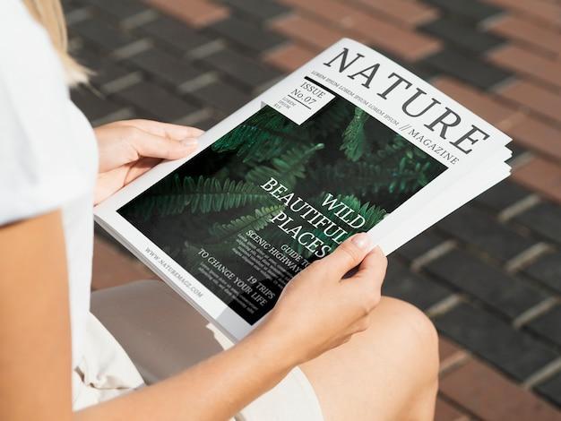 Manos sosteniendo una revista de naturaleza salvaje simulacro