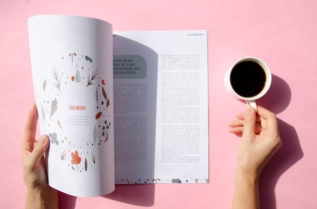 Manos sosteniendo una revista y una taza de café simulacro