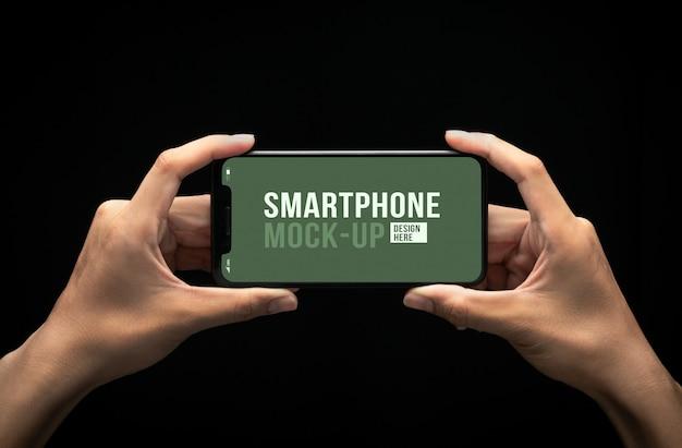 Manos sosteniendo teléfono inteligente moderno con plantilla de maqueta de pantalla