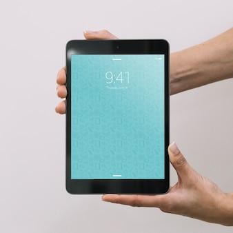 Manos sujetando mockup de tablet