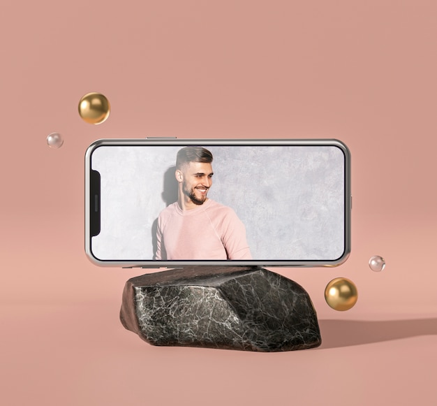 Maqueta 3d de teléfono móvil sobre roca de mármol