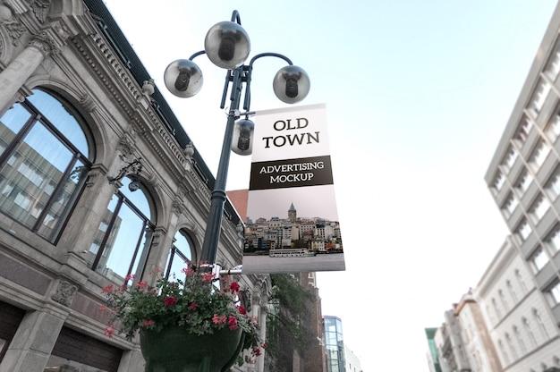 Maqueta de la bandera de publicidad negra clásica vertical al aire libre en la farola de la ciudad vieja