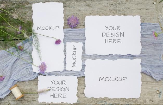 Maqueta de boda establece tarjetas con flores de color rosa en un corredor violeta y olr espacio de madera rústica