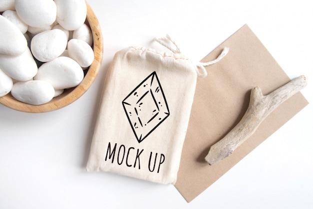 Maqueta de bolsa de algodón cubierta de tarot con sobre de papel artesanal de textura marrón y palo rústico