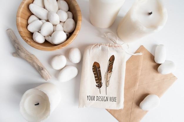 Maqueta de bolsa de algodón o bolsa y tazón con guijarros blancos y elementos boho en mesa blanca.