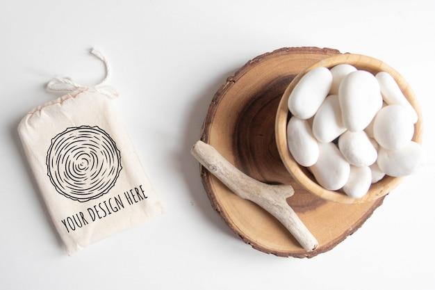Maqueta de bolsa o bolsa de algodón y tazón con guijarros blancos y sección de árbol cortado en madera sobre mesa blanca