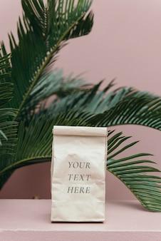 Maqueta de bolsa de papel en una habitación rosa pastel junto a una palmera