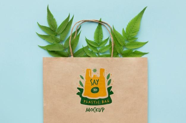 Maqueta de bolsa de papel de vista superior con hojas
