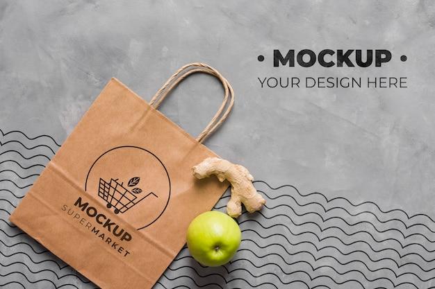 Maqueta de bolsa de papel de vista superior con manzana y jengibre