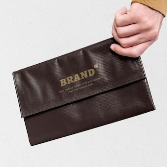 Maqueta de bolso de mano marrón sostenido por una mano de mujer