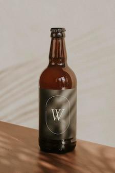 Maqueta de botella de cerveza marrón sobre superficie de madera