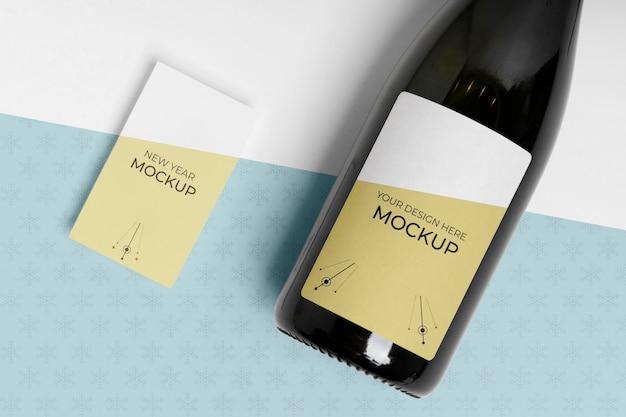 Maqueta de botella de champagne con tarjeta de visita con el mismo diseño