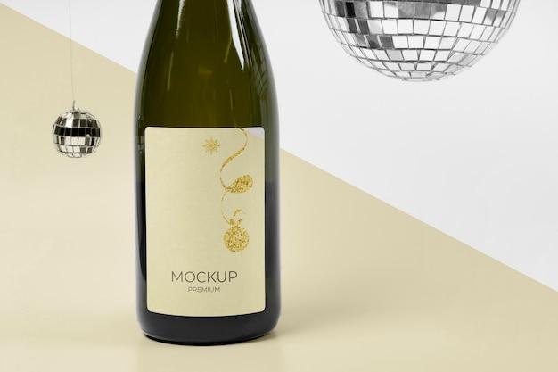 Maqueta de botella de champán y bolas de discoteca plateadas