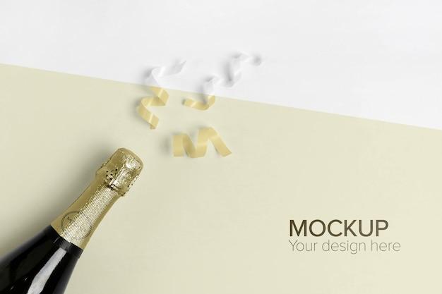 Maqueta de botella de champán y confeti amarillo