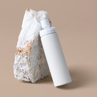 Maqueta de botella de spray blanco contra una roca