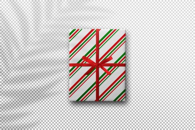 Maqueta de caja de regalo con diseño navideño con sombra de hojas de palmera