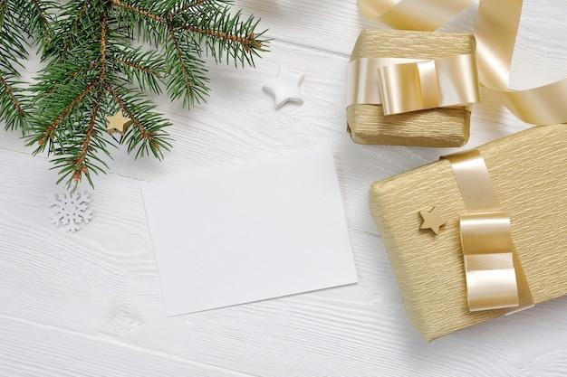 Maqueta de caja de regalo de navidad y vista superior de abeto y cinta dorada, flatlay