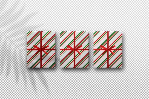 Maqueta de cajas de regalo de navidad con sombra de hojas de palma