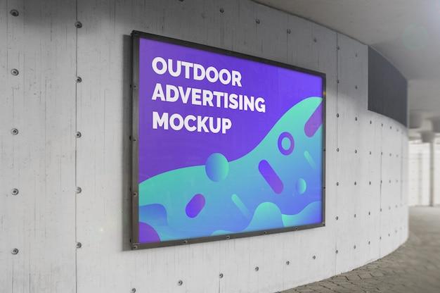 Maqueta de la cartelera horizontal de publicidad exterior de la calle de la ciudad en marco negro en el muro de hormigón