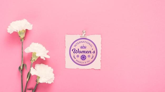 Maqueta de cartón con claveles sobre fondo rosa