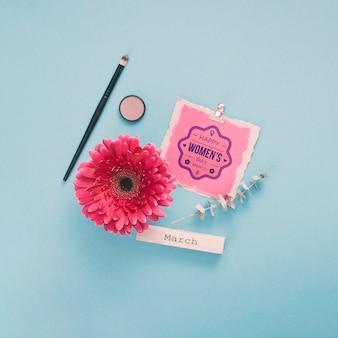 Maqueta de cartón con flores y maquillaje sobre fondo azul.