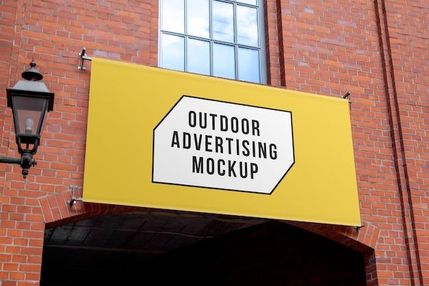 Maqueta de colgar carteles publicitarios horizontales al aire libre en la pared de ladrillo