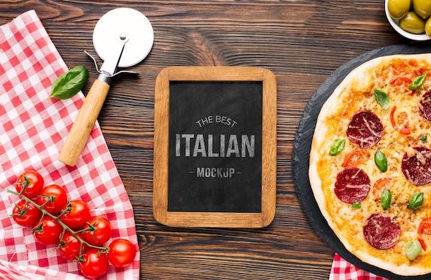 Maqueta de comida italiana con pizza y tomates.