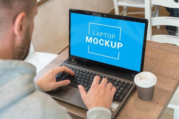 Maqueta de computadora portátil en el escritorio de la cafetería