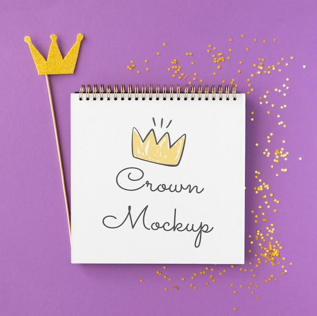 Maqueta de corona sobre fondo violeta con destellos