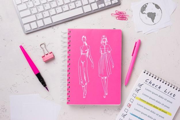 Maqueta de cuaderno plano con papelería cerca del teclado