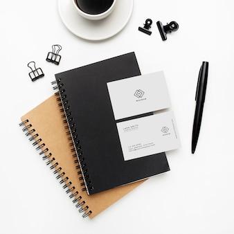 Maqueta de cuadernos y tarjetas de visita con elementos en blanco y negro sobre fondo blanco
