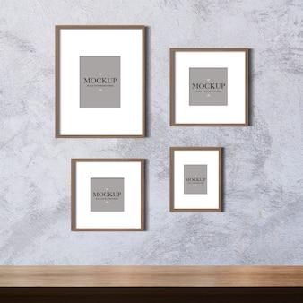 Maqueta de cuatro fotos en blanco en la pared de cemento
