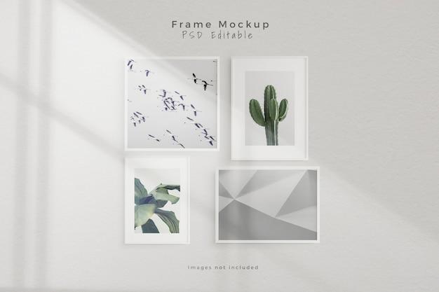 Maqueta de cuatro marcos de fotos vacíos en una habitación vacía de pared blanca