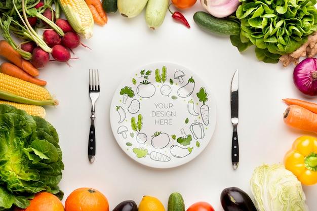 Maqueta y cubiertos con marco hecho de deliciosas verduras frescas