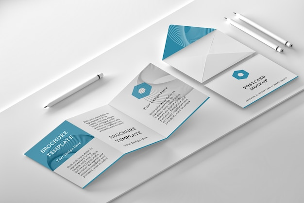 Maqueta de diseño isométrico con folleto tríptico, sobre abierto, tarjeta de mensaje y lápices