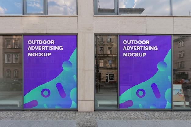 Maqueta de dos publicidades exteriores en marcos de ventanas en fachadas de edificios clásicos