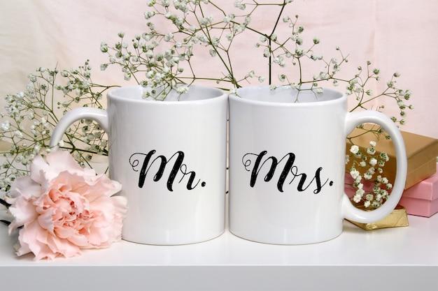 Maqueta de dos tazas de café con flores blancas
