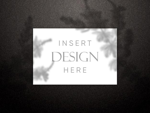 Maqueta editable con tarjeta en blanco sobre textura de brillo negro con superposición de sombras