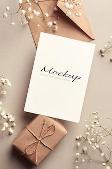 Maqueta estacionaria de tarjeta de felicitación con sobre, caja de regalo y flores blancas de hypsophila