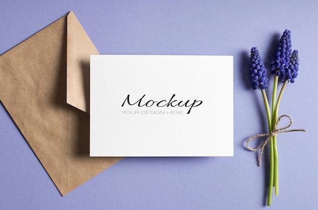 Maqueta estacionaria de tarjeta de felicitación con sobre y flores de muscari azul de primavera