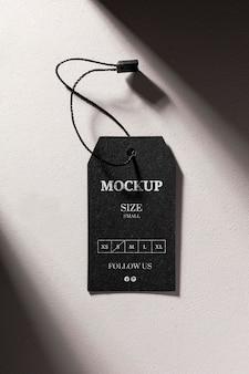 Maqueta de etiqueta de tamaño negro de ropa con sombras