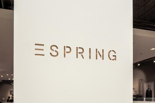 Maqueta del exclusivo y elegante logotipo de moda con corte de madera en 3d en la tienda o entrada de la tienda blanca