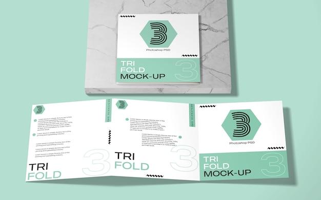 Maqueta de folleto tríptico cuadrado sobre mármol